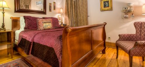 Camelot Bedroom with beautiful wood sleigh bed and regal burgundy bedding