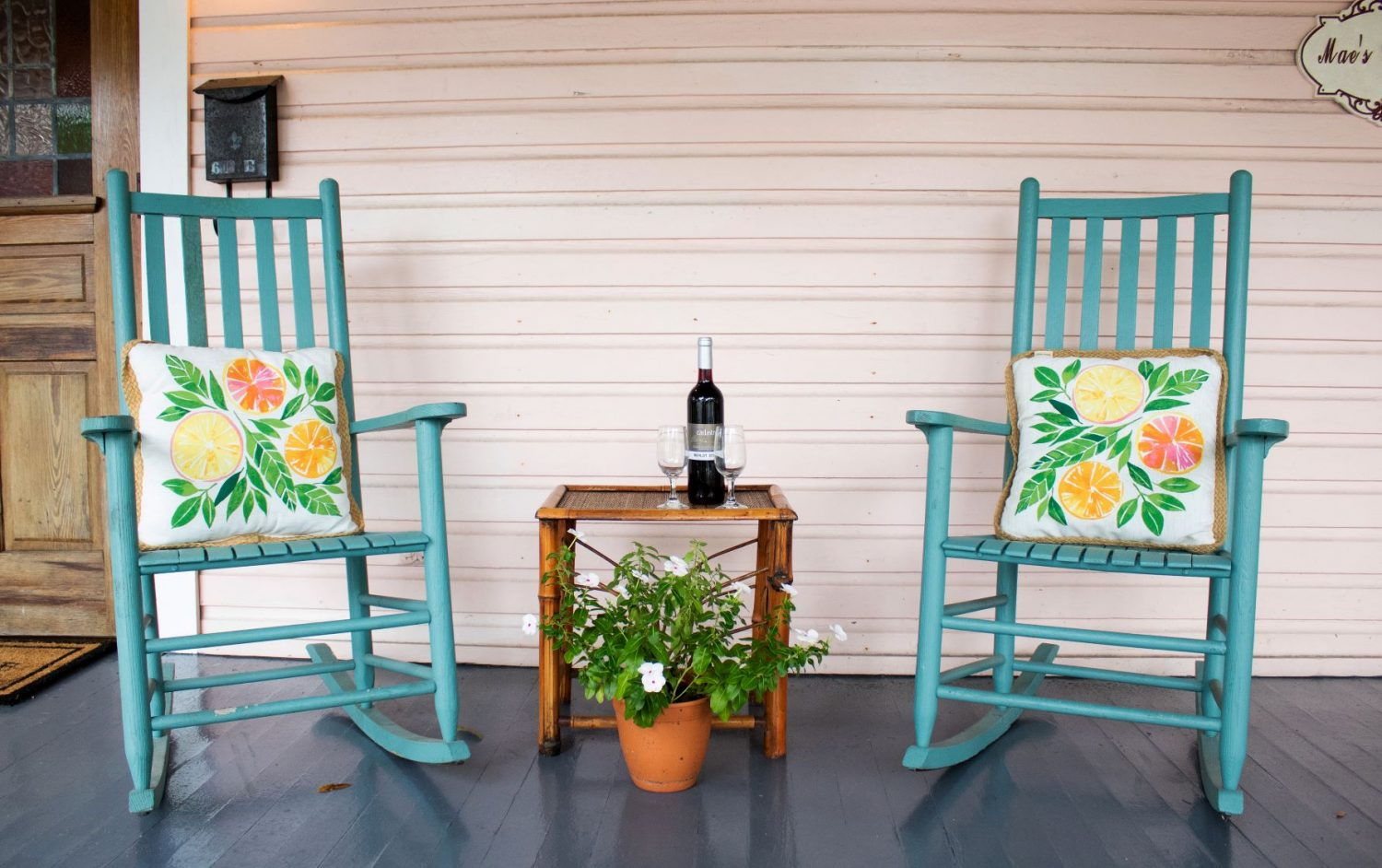 Patio Chairs with floral pillows and a bottle of beer in between
