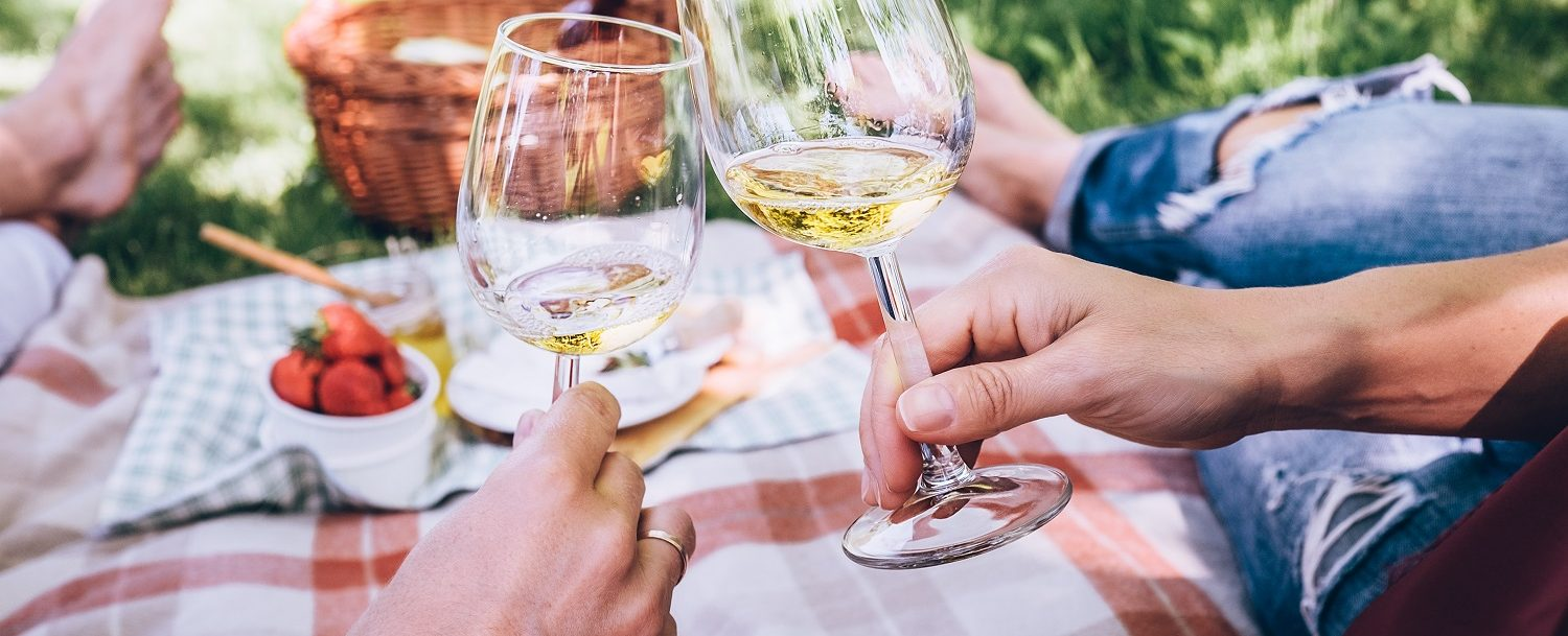 Couple in love drinks a white wine on summer picnic