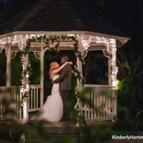 couple standing at gazebo wedding altar at night