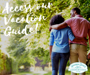 cute couple strolling outdoors beneath the trees. text reads access our vacation guide