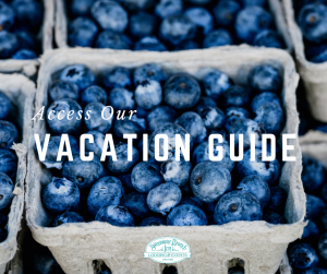 organic blueberries grown for wine text reads access our vacation guide