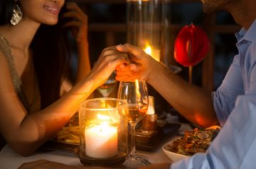 Romantic couple holding hands together over candlelight