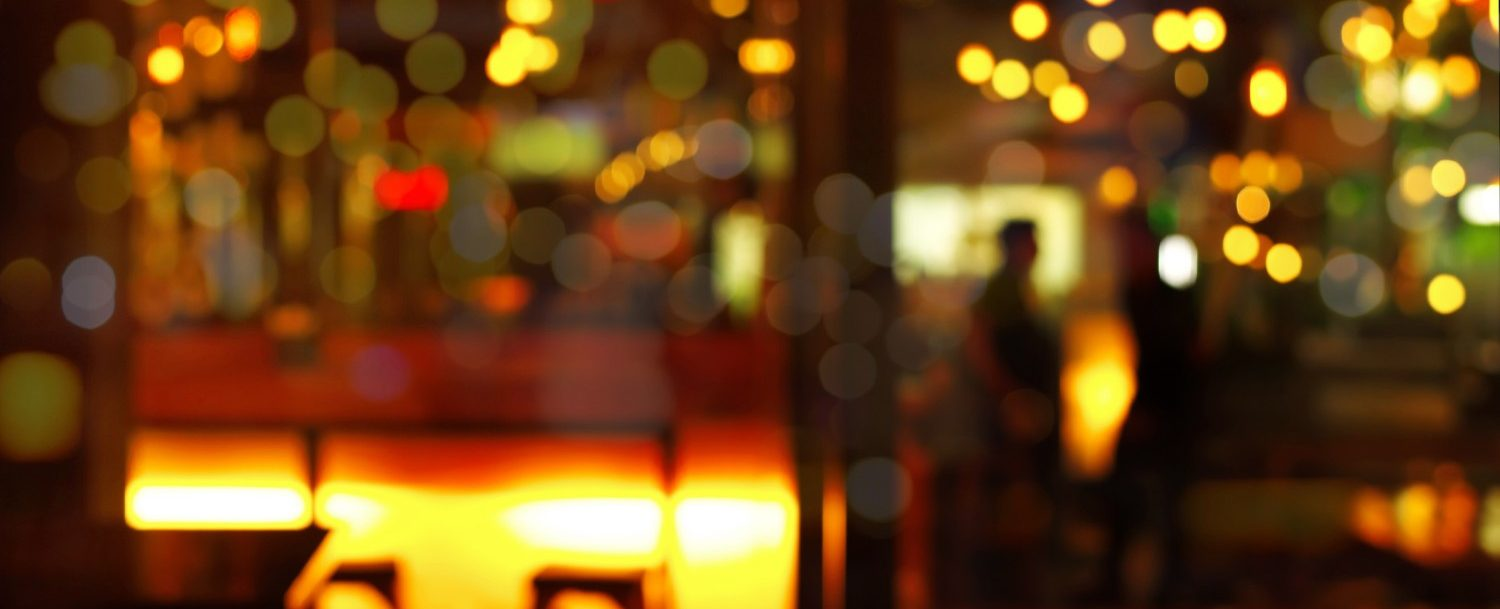 top of wood table with blur bokeh light with shadow of people in pub or bar in dark night background