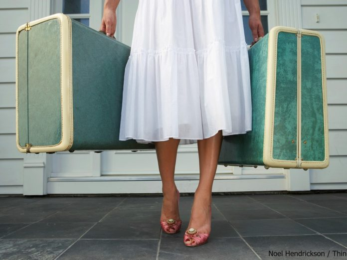 woman in a long, white skirt holding a large blue suitcase in each hand.