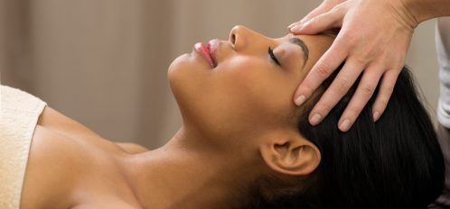 Closeup of young woman receiving professional head massage at spa